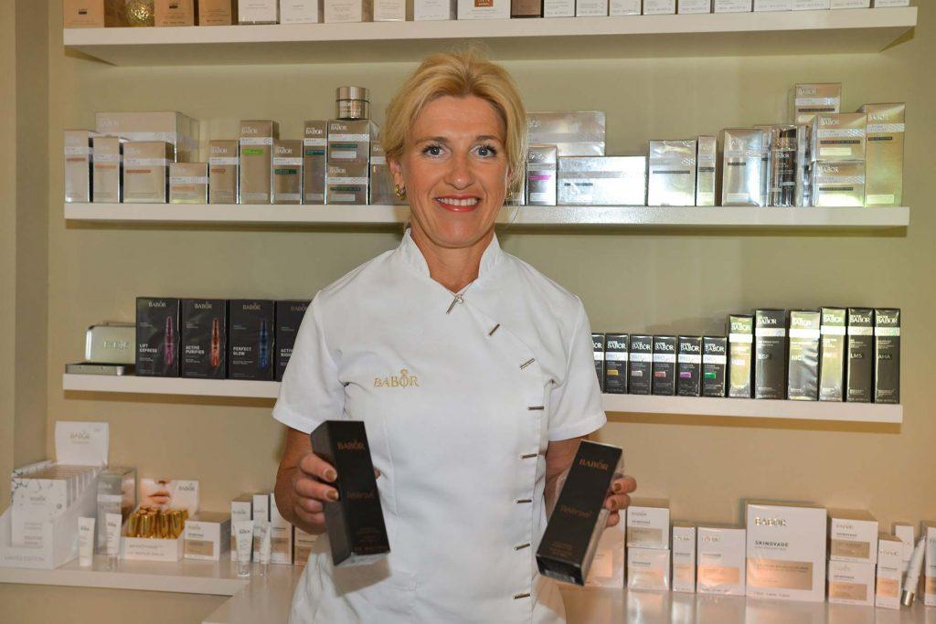 Eigenaar met producten in haar hand voor een vitrine met producten