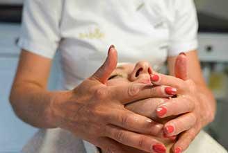 Handen die een vrouw een gezichtsbehandeling geven
