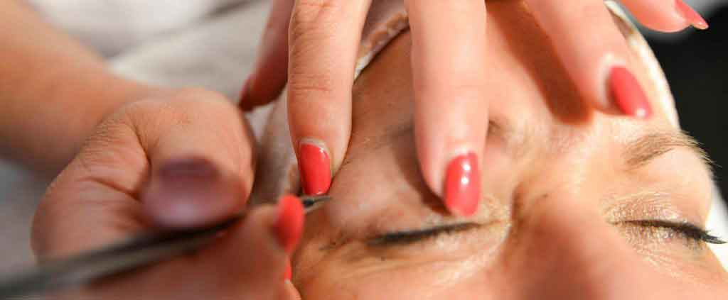 Vrouw laat wenkbrouwen epileren in de schoonheidssalon in Well