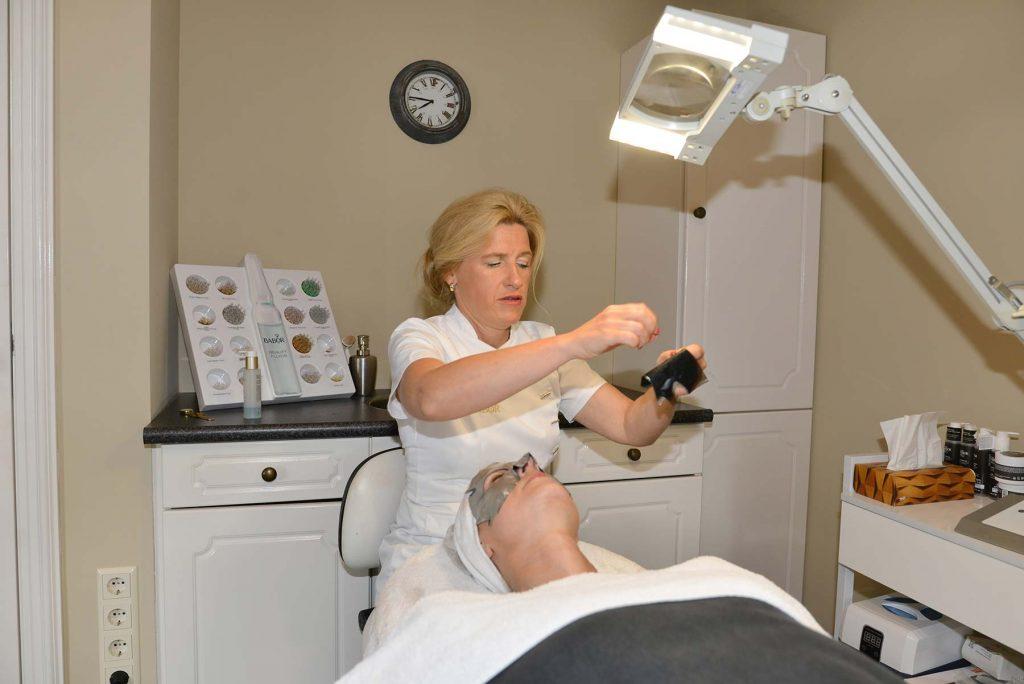 Eigenaar maakt apparatuur klaar voor gezichtsbehandeling