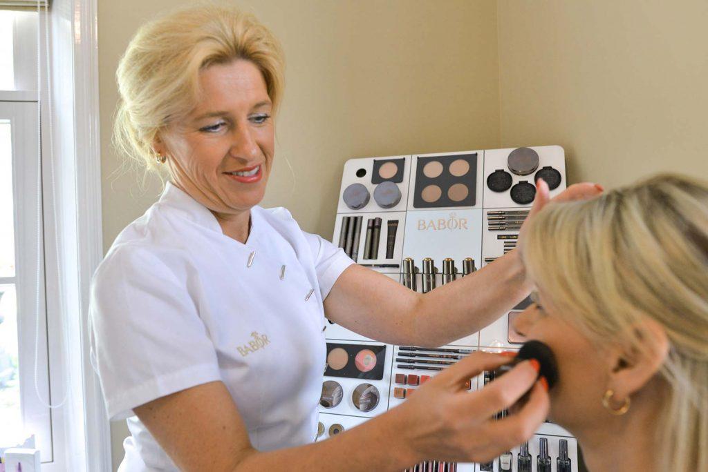 Eigenaar doet make-up op bij klant in de schoonheidssalon